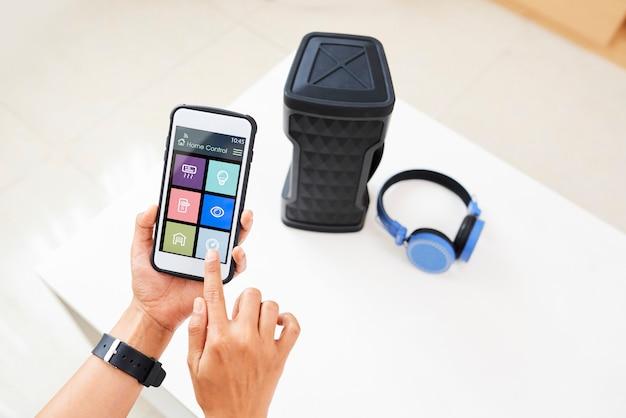 Frau, die smartphone-musikanwendung zum drahtlosen lautsprecher verbindet