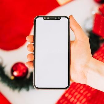 Frau, die smartphone über tabelle mit weihnachtsbaumdekoration hält