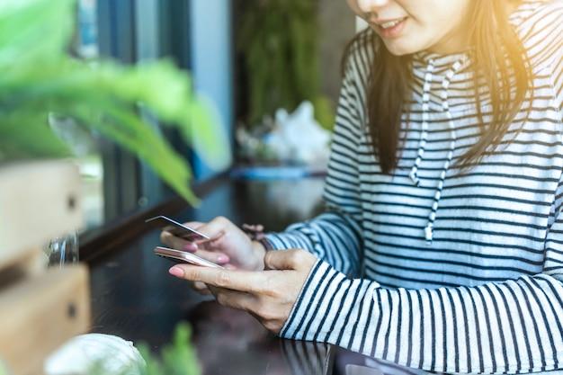 Frau, die smartphone und kreditkarte für online kaufen verwendet