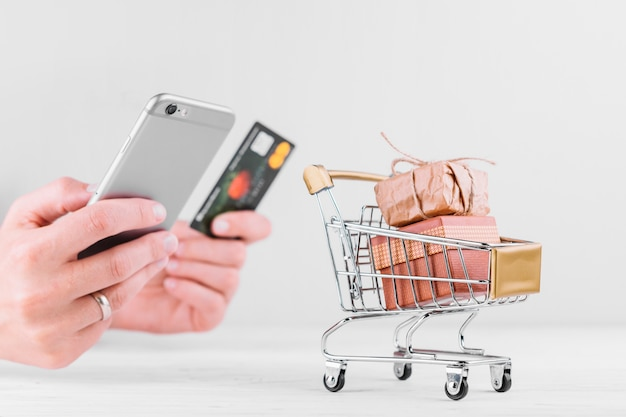 Frau, die smartphone und kreditkarte hält