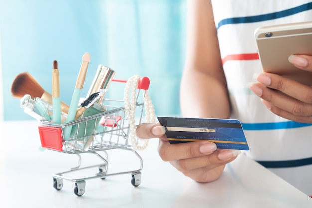 Frau, die smartphone- und kreditkarteneinkaufsschönheitseinzelteile verwendet. online-shopping, e-payment