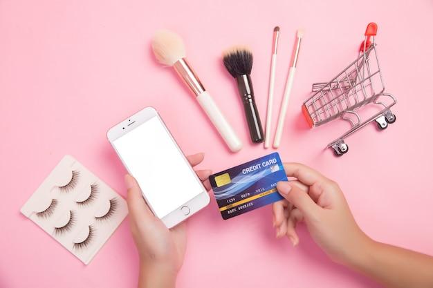 Frau, die smartphone- und kreditkarteneinkaufsschönheitseinzelteile verwendet