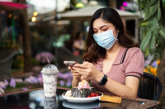 Frau, die smartphone und medizinische maske trägt