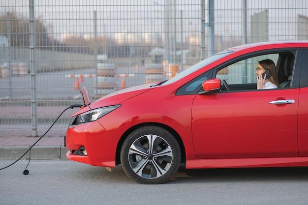 Frau, die smartphone und wartendes netzteil verwendet, verbinden sich mit elektrofahrzeugen zum laden der batterie im auto. positives junges mädchen, das am telefon spricht, sitzt im elektroauto und lädt auf.