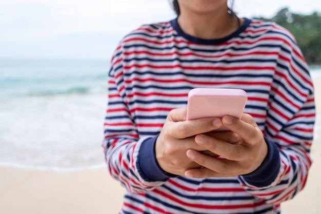 Frau, die smartphone verwendet, um studie im urlaubstag am strandhintergrund zu arbeiten.