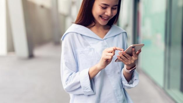 Frau, die smartphone, während der freizeit verwendet. das konzept der verwendung des telefons ist im alltag unerlässlich