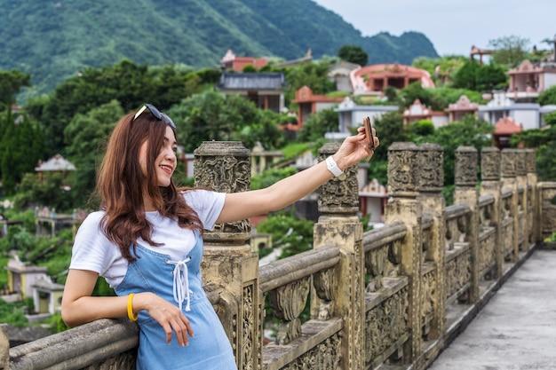Frau, die smartphone zum selfie foto in jiufen, taiwan verwendet
