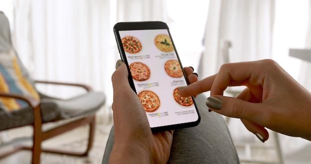 Frau, die smartphonebildschirm durchsucht, der pizza zu hause online bestellt