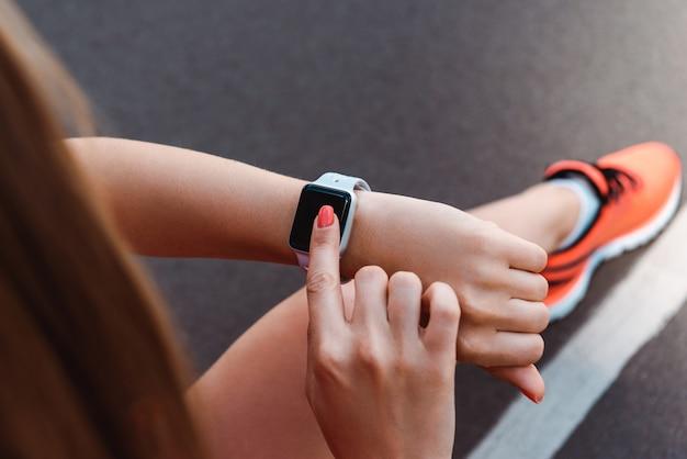 Frau, die smartwatch auf laufbahn verwendet