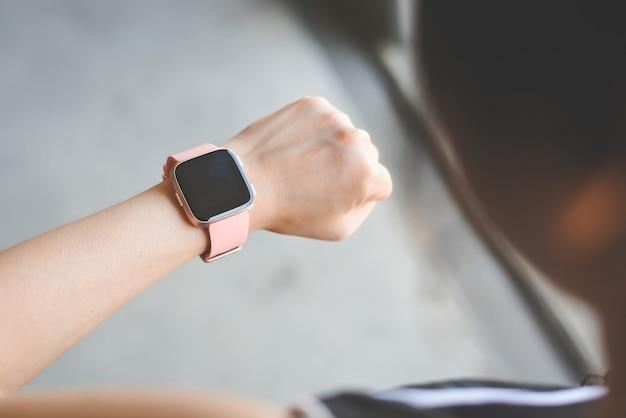 Frau, die smartwatch überprüft