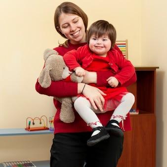 Frau, die smiley-kind mit down-syndrom hält