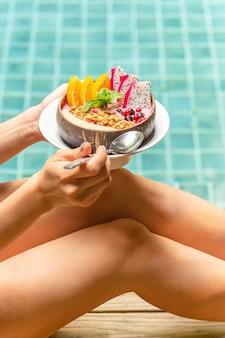 Frau, die smoothie-schüssel mit gemischten früchten durch schwimmbad hält.