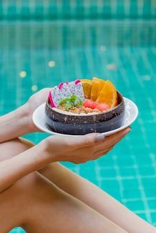 Frau, die smoothie-schüssel und früchte durch schwimmbad hält.