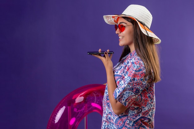 Frau, die sommermütze und rote sonnenbrille hält, die aufblasbaren ring hält, der sprachnachricht unter verwendung des mobiltelefons sendet, das seitlich mit glücklichem gesicht auf lila steht