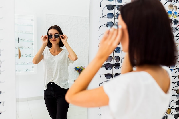 Frau, die sonnenbrille im spiegel überprüft
