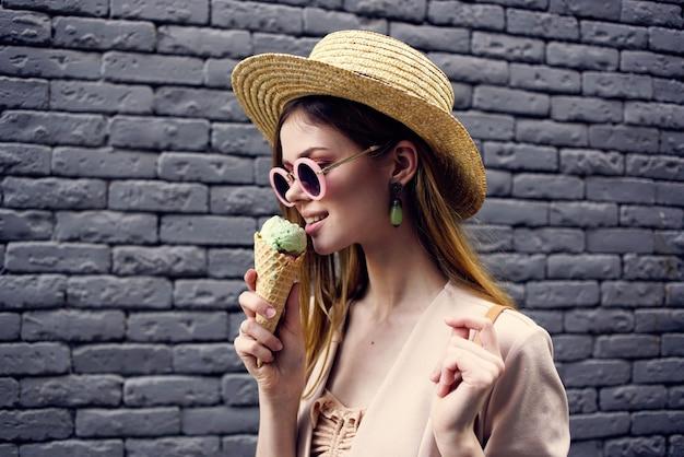 Frau, die sonnenbrille und hut beschnitten ansicht städtische art ziegelmauer trägt.