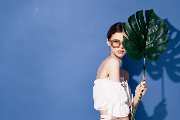 Frau, die sonnenbrillenpalmenkosmetik-sommerreise blaue wand trägt.