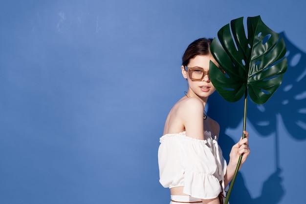Frau, die sonnenbrillenpalmenkosmetik-sommerreise blauen hintergrund trägt.