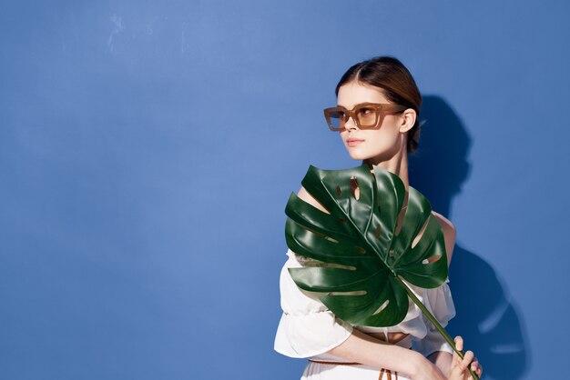 Frau, die sonnenbrillenpalmenkosmetiksommerreise blauen hintergrund trägt.