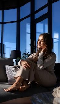 Frau, die sonnenlicht durch panoramafenster genießt