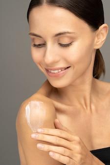 Frau, die sonnenschutzcreme oder kosmetische feuchtigkeitslotion auf perfekte hydratisierte haut auf schulter aufbringt