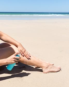 Frau, die sonnenschutzmittel auf ihren beinen anwendet.