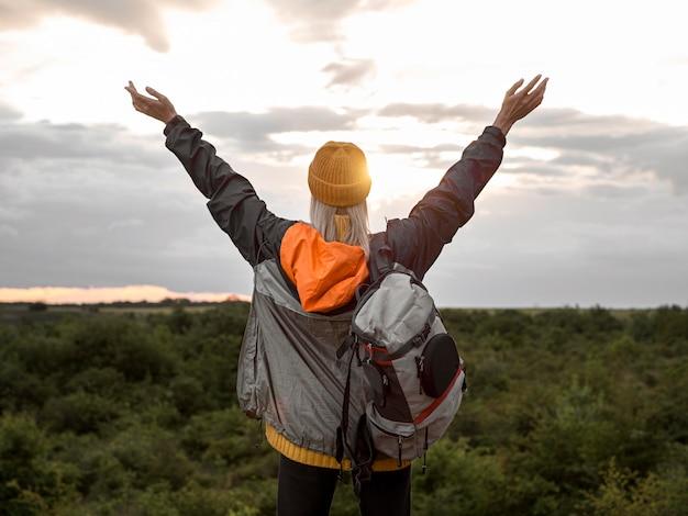 Frau, die sonnenuntergang am berg genießt