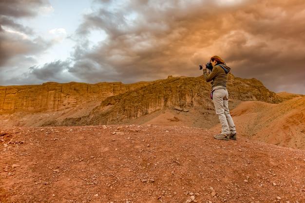 Frau, die sonnenuntergangslandschaft in marrakesch fotografiert