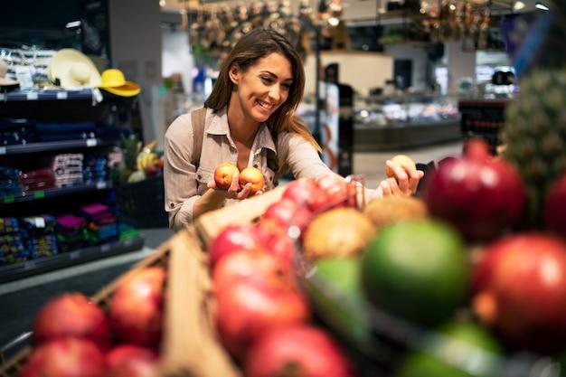 Frau, die sorgfältig frucht für ihren salat am supermarkt wählt