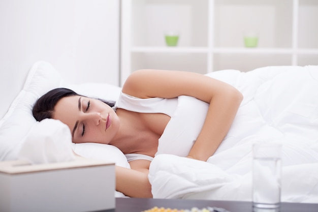 Frau, die spät am wochenende schläft, müde von der langen arbeitswoche, die auf plüschiger weißer bettdecke ruht