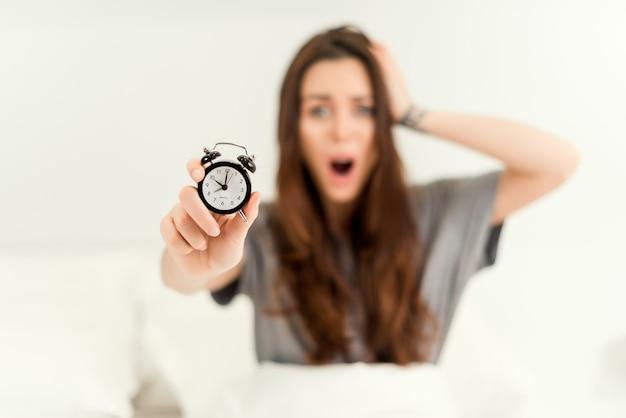 Frau, die spät für arbeit morgens mit wecker im fokus aufwacht