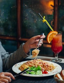 Frau, die spaghetti mit truthahnsalami und frischem salat auf gabel dreht