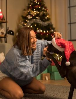Frau, die spaß an weihnachten mit ihrem hund trägt, der weihnachtsmütze trägt