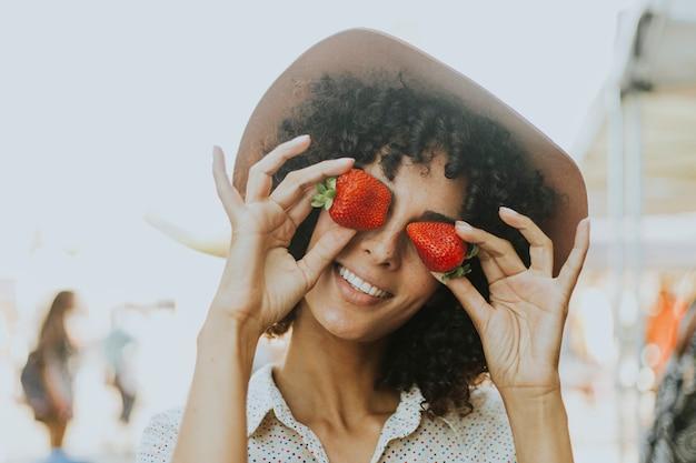 Frau, die spaß mit erdbeeren hat
