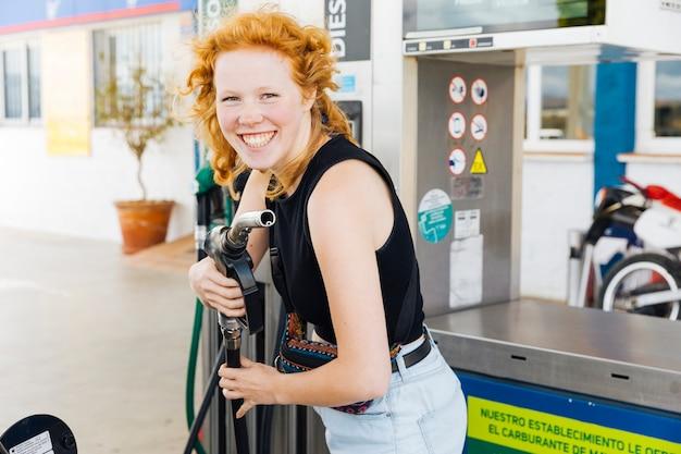 Frau, die spaß mit füllender gewehr hat und kamera betrachtend lächelt