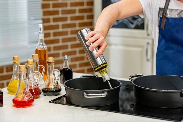 Frau, die speiseöl von der flasche in bratpfanne auf ofen gießt