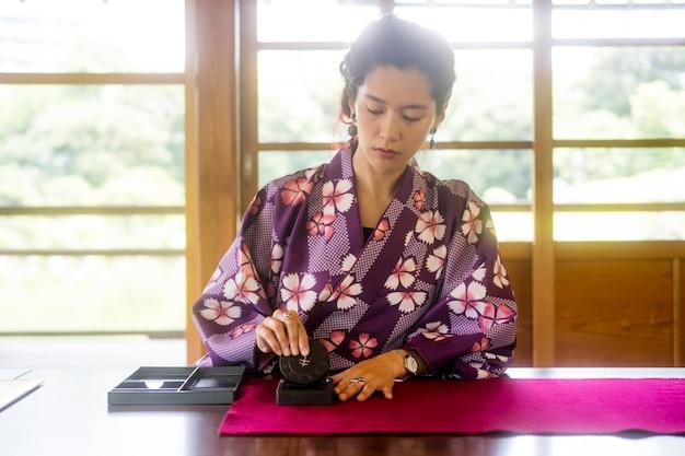 Frau, die spezielles zubehör für japanische kunst verwendet