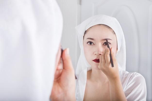 Frau, die spiegel schaut und bleistiftmake-upbraue verwendet