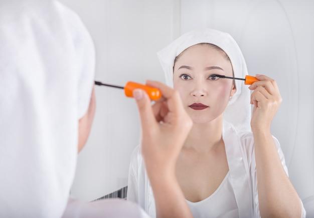 Frau, die spiegel schaut und wimperntusche auf ihren wimpern anwendet