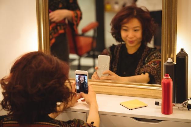 Frau, die spiegel selfie am friseursalon nimmt