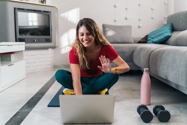Frau, die sport auf einer matte nach online-kursen mit laptop zu hause macht