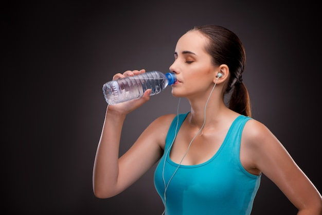 Frau, die sport mit flasche süßwasser tut