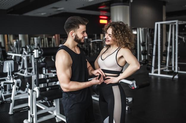 Frau, die sport trägt, trägt mit gürtel und ihrem personal trainer während des trainings im fitnessstudio