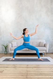 Frau, die sport zu hause ausübt, das im yoga während des stehens streckt