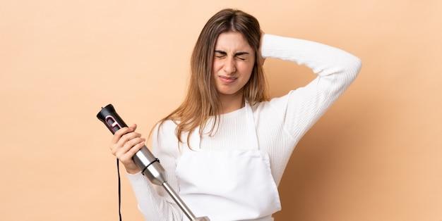 Frau, die stabmixer über isolierte frustrierte und bedeckende ohren verwendet