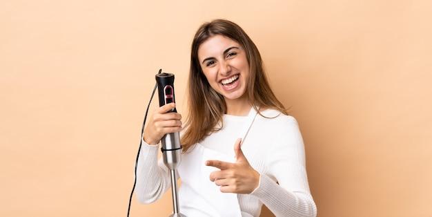 Frau, die stabmixer verwendet, zeigt nach vorne und lächelt