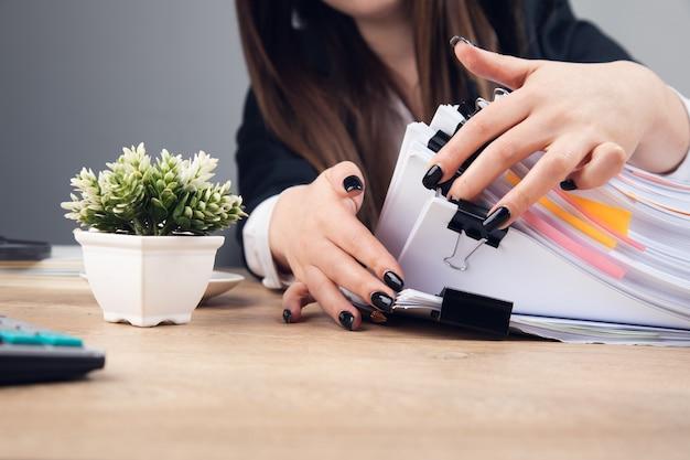 Frau, die stapel geschäftsdokumente auf tisch hält