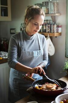 Frau, die steak in der küche kocht