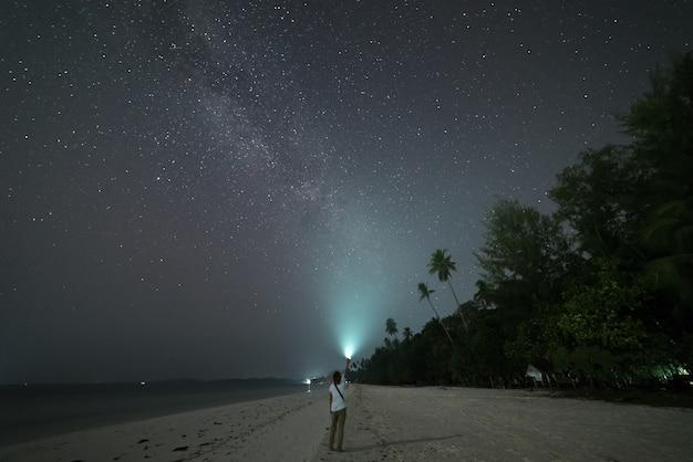 Frau, die sterne und milchstraße auf sandstrand betrachtet