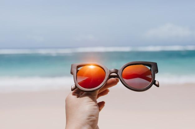 Frau, die stilvolle sommersonnenbrille über meer hält. außenfoto der weiblichen hand mit den gläsern am strand.